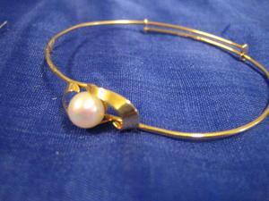 Armring i 18 karat guld med odlad pärla.