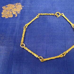 Armband i 18 karat guld.Stavar med rågulds yta.