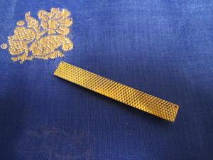 Slipshållare i 18 karat guld med slipat rutmönster.
