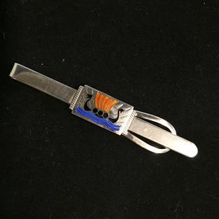 Här en Slipshållare i  i äkta silver med vikingaskepp i emalj från-50talet.  Storlek: 7cm lång.  Vikingaskepp i blå-röd-svart emalj. Tydliga svenska stämplar, kattfot och S.  Mycket ovanlig !